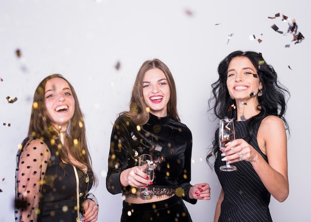 Happy women standing with champagne glasses under spangles Free Photo