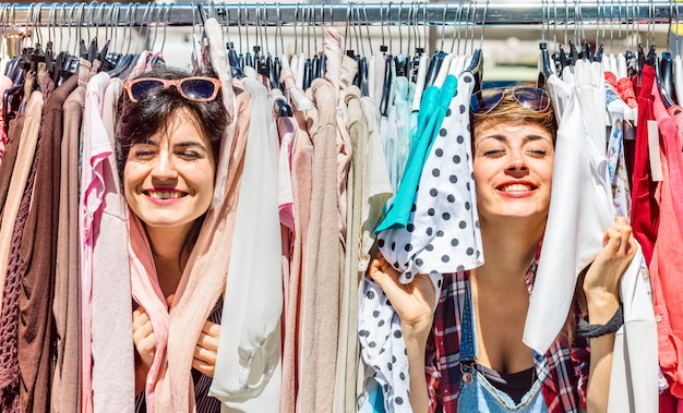 Happy women at weekly flea market - female friends having fun together shopping cloth on sunny day Premium Photo