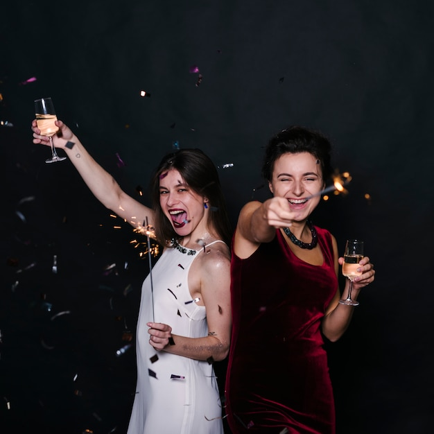 Happy women with champagne glasses and sparklers Free Photo