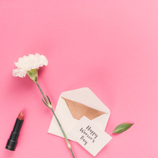Happy womens day inscription with envelope and flower on pink table Free Photo