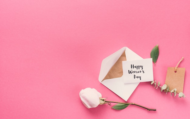 Happy womens day inscription with envelope and flower on table Free Photo