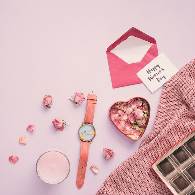 Happy womens day inscription with rose petals and watch Free Photo
