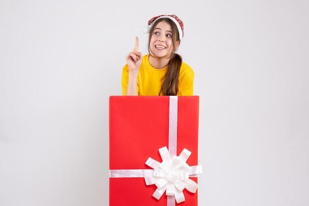 화이트에 큰 크리스마스 선물 뒤에 서있는 산타 모자와 함께 행복 한 크리스마스 소녀 무료 사진