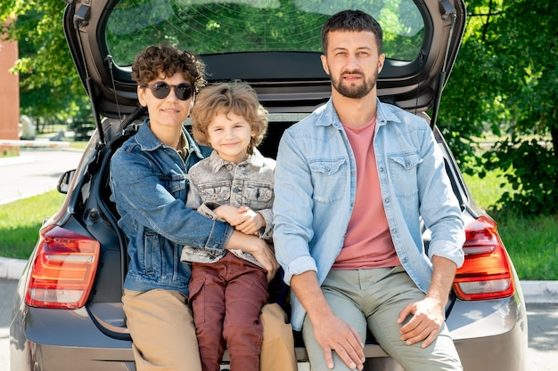 Happy young affectionate family of father, mother and son of elementary age sitting in the car trunk on sunny summer day Premium Photo