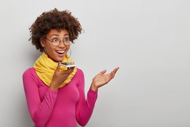 행복 한 젊은 아프리카 아가씨 스마트 폰 음성 인식을 사용 하 고 손바닥을 제기 하 고 광범위 하 게 흰색 배경 위에 절연 미소 무료 사진