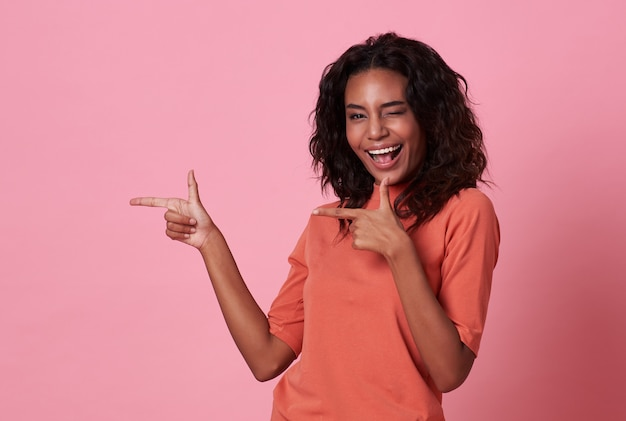 Happy young african woman standing with her finger pointing on pink background Premium Photo