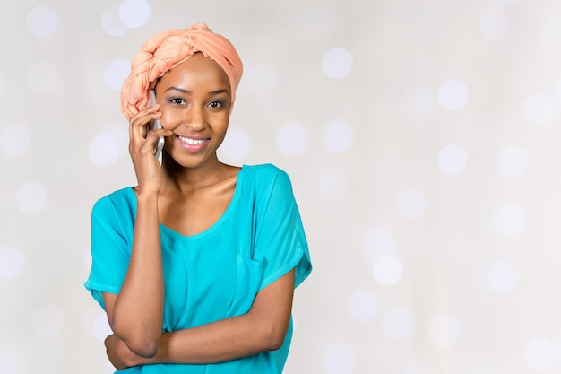 Happy young african woman talking on cell phone Premium Photo