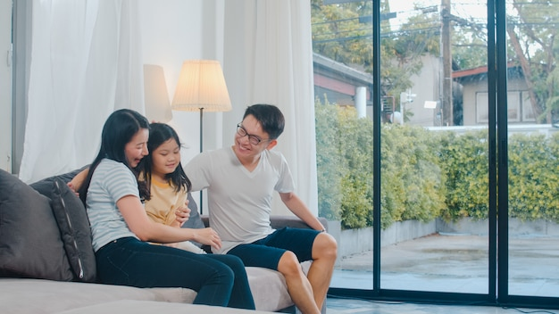 Happy young asian family play together on couch at home. chinese mother father and child daughter enjoying happy relax spending time together in modern living room in evening. Free Photo