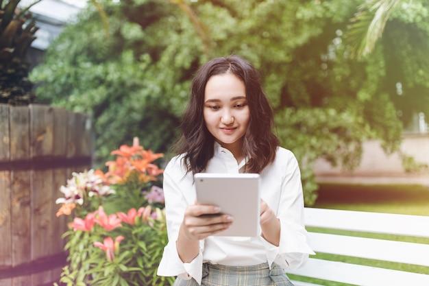 Счастливая молодая азиатская студентка в парке, работающем на ноутбуке Premium Фотографии