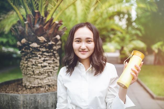 Счастливая молодая азиатская женщина в парке с многоразовой пластиковой бутылкой Premium Фотографии