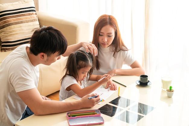 幸せな若いアジアの女の子と彼女の素敵な両親は宿題の割り当てを教育し、一緒に充実した時間を過ごしました。アジアの家族、社会的距離、ホームスクーリング、在宅勤務または愛の概念 Premium写真