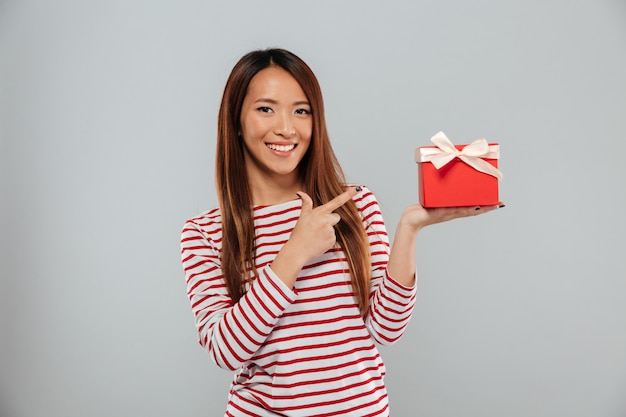 Happy young asian lady standing isolated holding gift and pointing. Free Photo