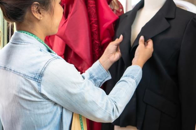 Счастливый молодой азиатский модельер портнихи женщины проверяет завершение для костюма и платья в выставочном зале. концепция успеха молодого предпринимателя в модном бизнесе. Premium Фотографии