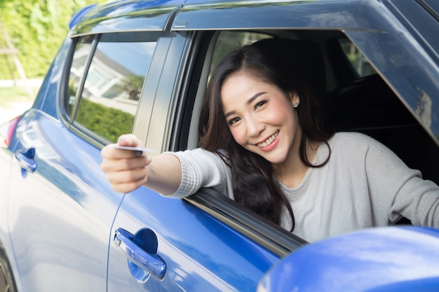 Happy young asian woman holding payment card or credit card Premium Photo