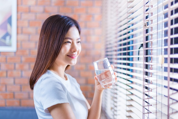 Premium Photo | Happy young asian woman relaxing at home holding a cold  glass of water to drink