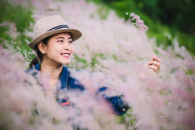 Happy young asian woman sitting on grass field Premium Photo