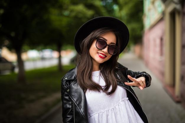 Счастливая молодая азиатская женщина принимая selfie с знаком мира на улице города. Бесплатные Фотографии