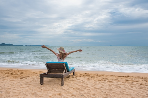 Happy young asian woman with hat relaxing on beach chair and raised hands up. Premium Photo