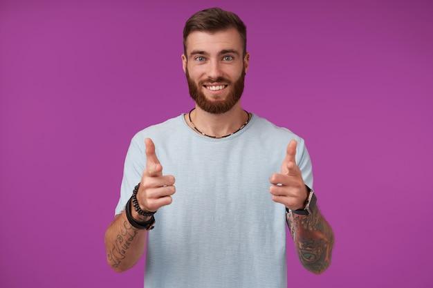 Felice giovane attraente brunetta uomo con barba allegramente e sorridente, alzando le mani con i pollici e mostrando le sue piacevoli emozioni, isolato su viola Foto Gratuite