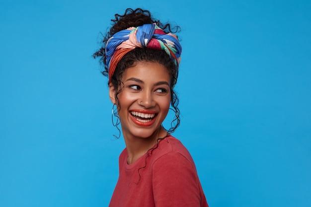 青い壁に隔離された彼女の肩越しに喜んで見ながら元気に笑って集まった髪を持つ幸せな若い魅力的な黒髪の女性 無料写真