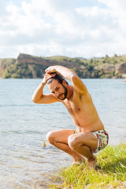 Happy young bearded man wetting hair on lake Free Photo