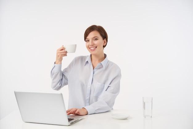 お茶と手を上げて、白い上に座って、魅力的な笑顔で元気に見えるナチュラルメイクで幸せな若い美しい茶色の髪の女性 無料写真