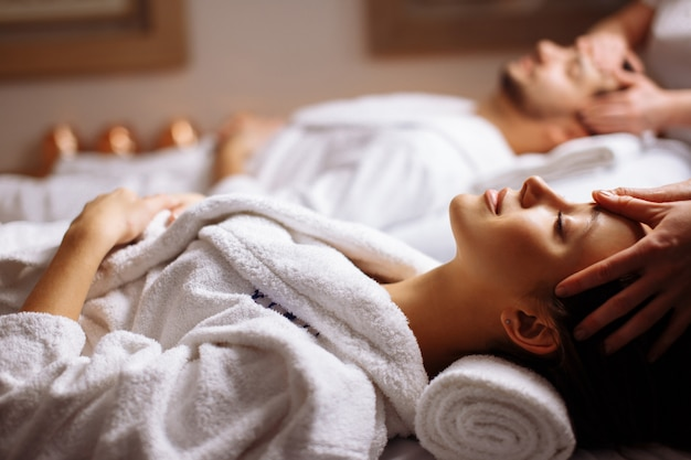 Happy young beautiful couple enjoying head massage at the spa Premium Photo