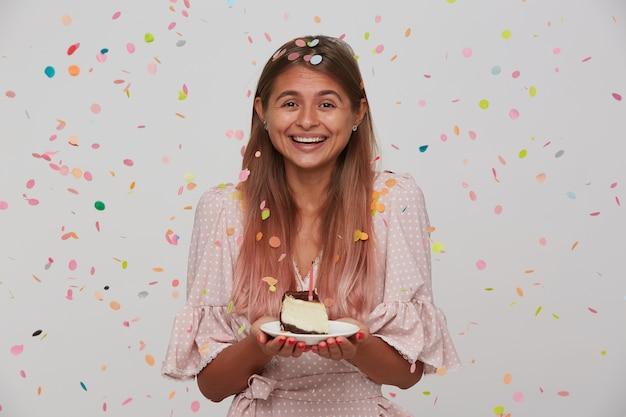 Счастливая молодая красивая длинноволосая женщина показывает свои приятные эмоции во время празднования дня рождения, позитивно улыбаясь с тортом в поднятых руках, позирует над белой стеной Бесплатные Фотографии