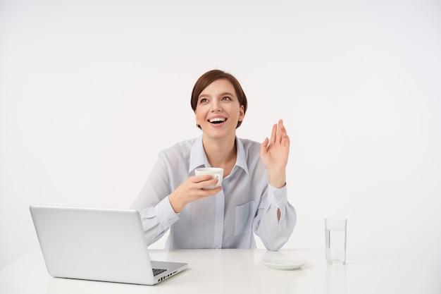 コーヒーを飲みながら、白で隔離のハロージェスチャーで彼女の手のひらを上げながら嬉しそうに笑っている自然なメイクで幸せな若い美しい短い髪の女性 無料写真