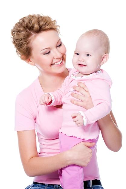 Счастливая молодая красавица мать с привлекательной улыбкой держит своего ребенка - изолированные на белом Бесплатные Фотографии
