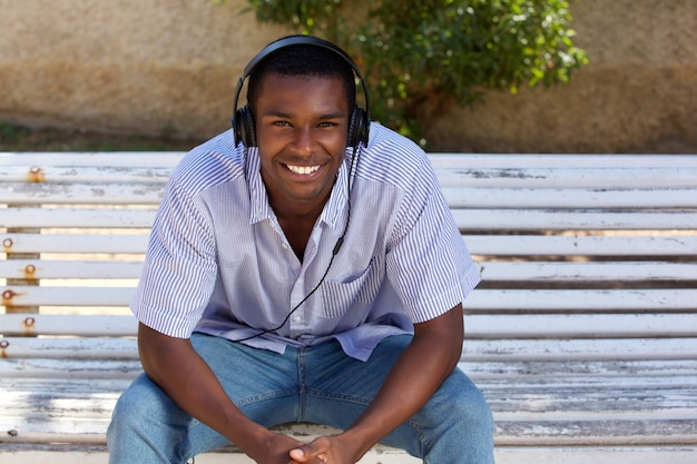 Happy Young Black Man Sitting On Park Bench With Headphones