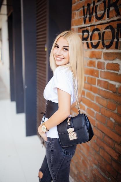背中に笑みを浮かべて、オフィスのレンガの壁に対して探しているカジュアルな服を着て幸せな若いブロンドの女性 無料写真