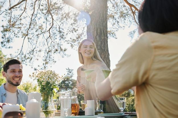Счастливая молодая блондинка берет пластиковый контейнер с салатом за сервированным столом во время ужина со своими друзьями под сосной Premium Фотографии
