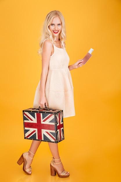 英国印刷スーツケースを持って幸せな若いブロンドの女性 無料写真