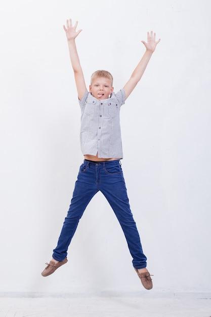 白い背景を飛び越えて幸せな少年 無料写真