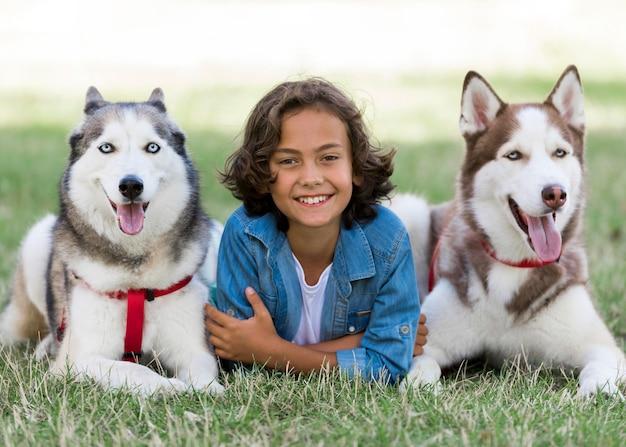 Felice giovane ragazzo in posa con i suoi cani al parco Foto Gratuite