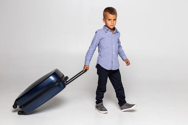 白い壁に分離された黒のスーツケースの後ろに座って幸せな少年。 無料写真