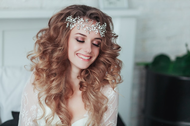 Happy young bride in tiara and lingerie laughing. close portrait. Free Photo
