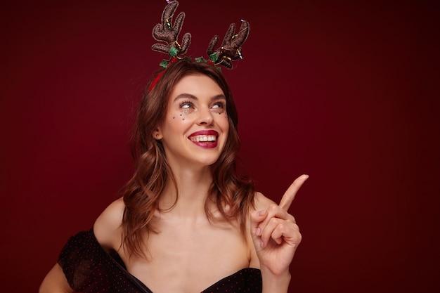 크리스마스 테마 파티를 즐기고, 집게 손가락으로 유쾌하게 위쪽으로 보여주는 그녀의 얼굴에 축제 메이크업과 은색 별이있는 행복 한 젊은 갈색 머리 쾌활한 여자 무료 사진