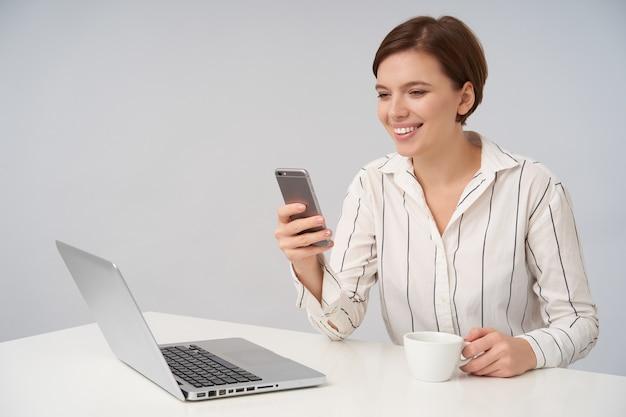 Felice giovane donna dai capelli castani con trucco naturale mantenendo il telefono cellulare in mano alzata e sorridente ampiamente mentre guarda lo schermo, posa su bianco con una tazza di tè Foto Gratuite