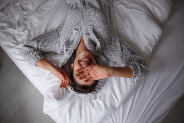 Счастливая молодая брюнетка-дама нежится в своей постели рано утром, лежа на белом постельном белье и держит руки на лице, весело улыбается и находится в хорошем настроении Бесплатные Фотографии