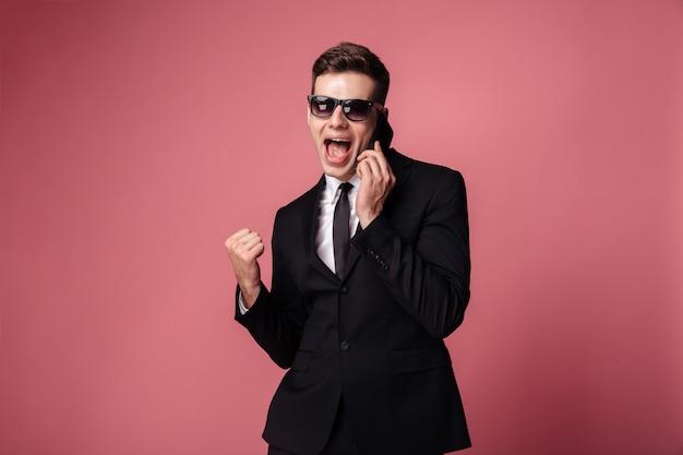 Счастливый молодой бизнесмен, говорить по телефону сделать победитель жест. Бесплатные Фотографии