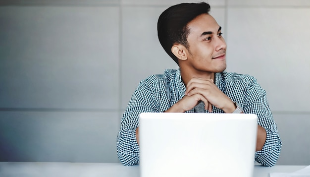 Happy young businessman working on computer laptop in office Premium Photo
