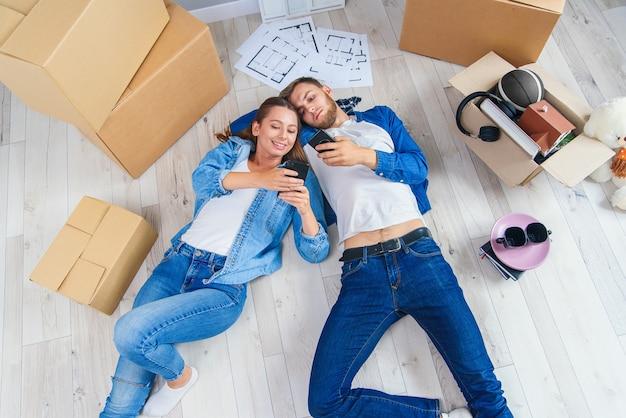 幸せな若い白人カップルは木製の床に横たわって、新しい家に移動しながら休憩を持っているphonesduringでメッセージング。 Premium写真