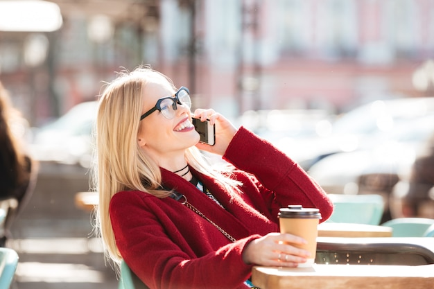 Happy young caucasian lady talking by phone drinking coffee. Free Photo