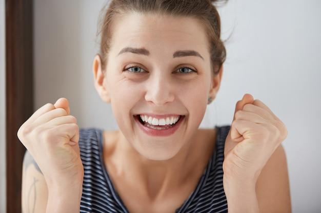 Счастливая молодая кавказская женщина разрывается от радости и удовольствия. красивая девушка с голубыми глазами сжимает кулаки в победном мышлении, улыбается с широко открытым ртом, показывая свои идеальные белые зубы. Бесплатные Фотографии