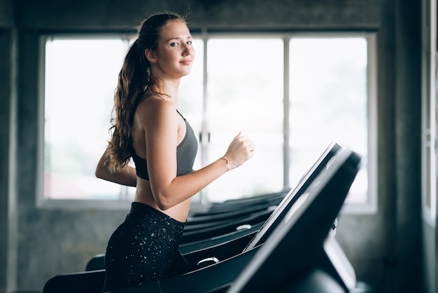 Happy young caucasian woman doing cardio by run on treadmill in gym Premium Photo