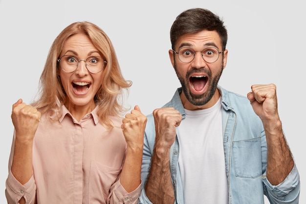 Счастливые молодые коллеги или деловые партнеры радуются успеху, сжимают кулаки и торжествующе восклицают Бесплатные Фотографии