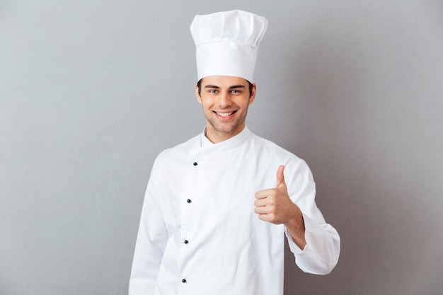 I giovani felici cucinano in uniforme che mostra i pollici su. Foto Gratuite