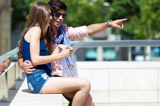 ストリートでデジタルタブレットでインターネットを閲覧している幸せな若いカップル Premium写真
